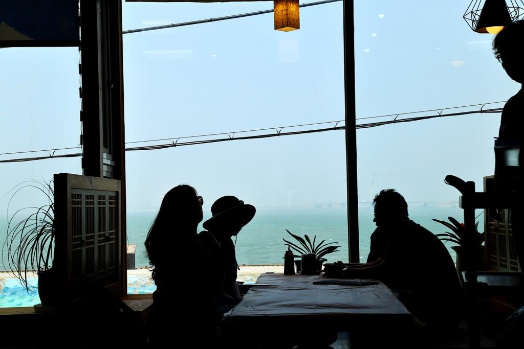 창가 옆 자리에 앉아 바다전망을 보고 있는 사람들