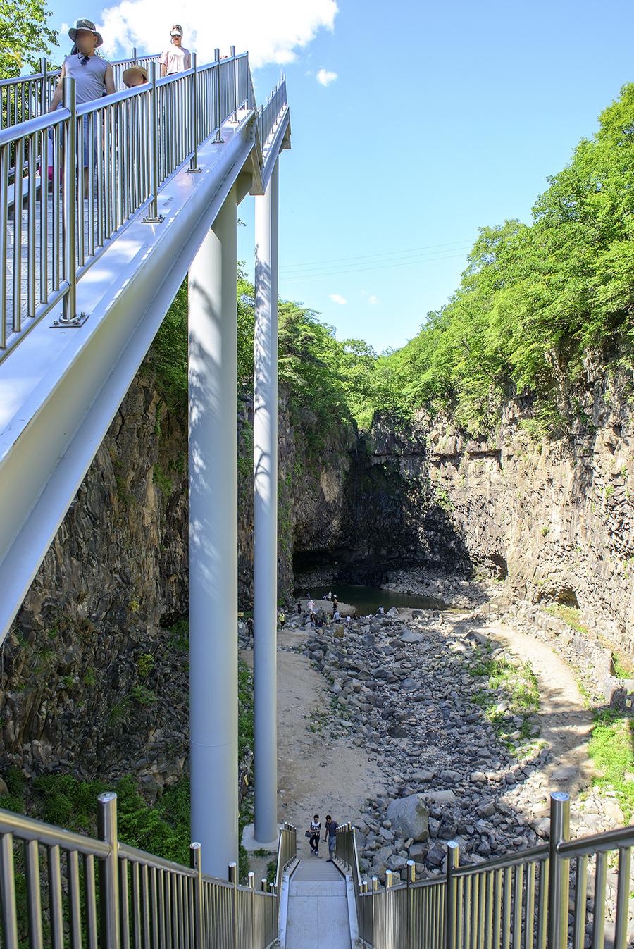 계단길을 내려가는 사람뒤로 보이는 재인폭포