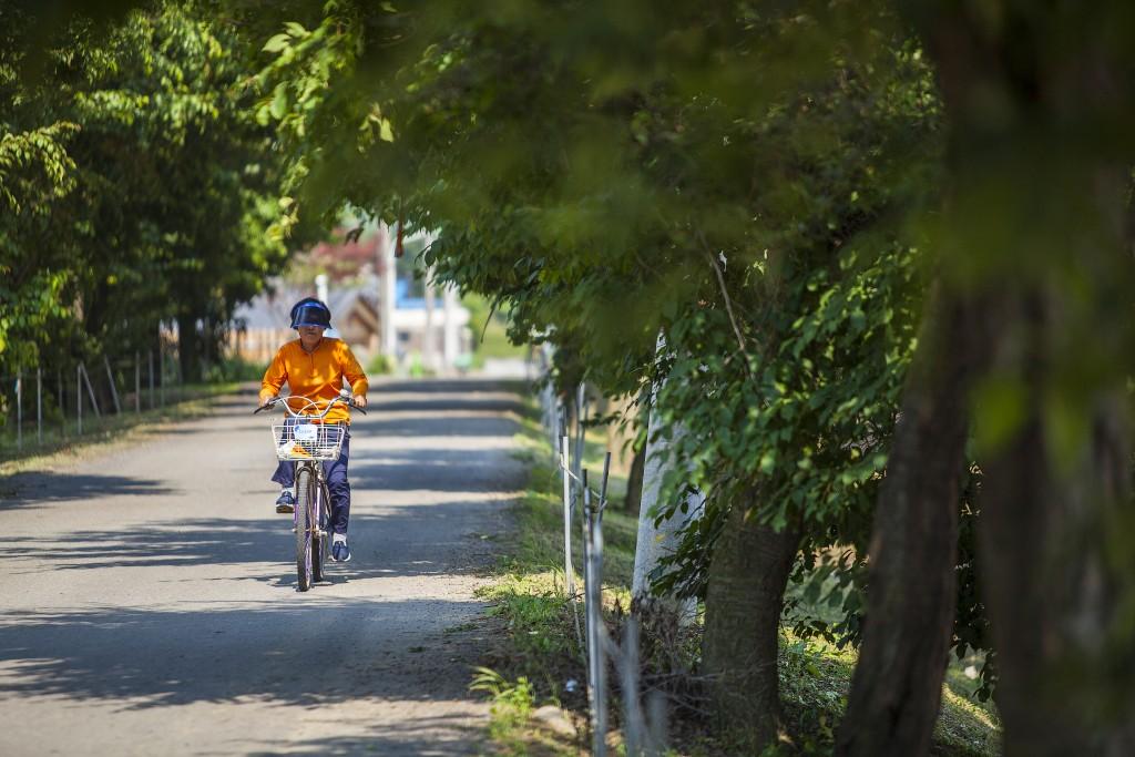 숲길을 달리고 있는 자전거를 탄 아주머니