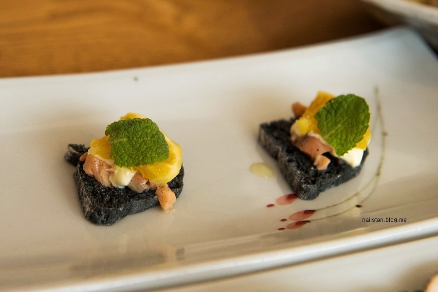 검은 색의 빵 위에 과일, 연어를 올린 카나페
