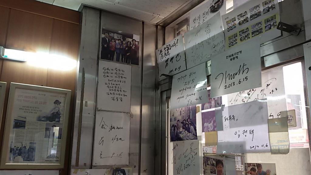 유명인들의 사인과 사진이 붙어있는 벽면