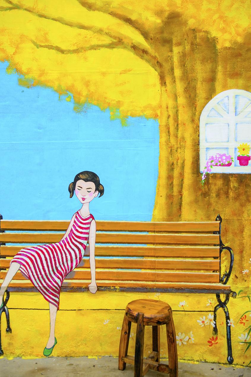 벤치에 앉아있는 여자의 모습 벽화