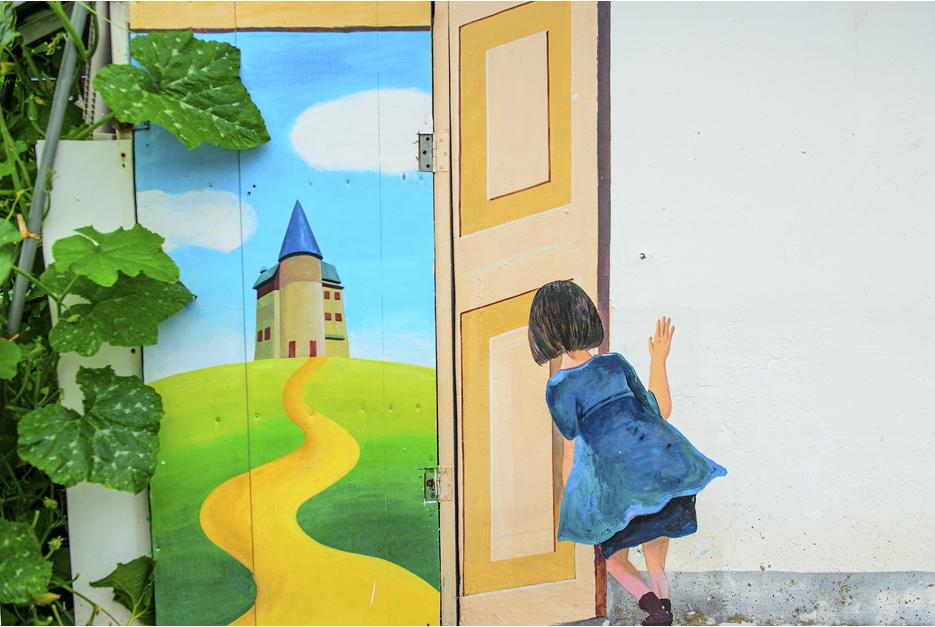 열려진 문 뒤 성을 보고있는 소녀벽화